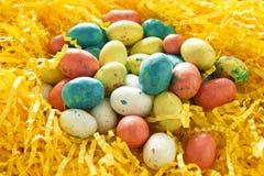 Huevos de Pascua del caramelo en hierba amarilla brillante Imágenes de archivo libres de regalías