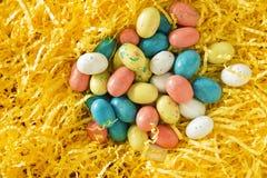 Huevos de Pascua del caramelo en hierba amarilla brillante Foto de archivo