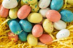 Huevos de Pascua del caramelo en hierba amarilla brillante Fotos de archivo