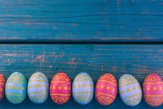 Huevos de Pascua del chocolate en fila, banco azul, fondo de pascua imagenes de archivo