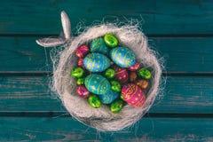 Huevos de Pascua del chocolate en un cuenco, banco verde imagenes de archivo