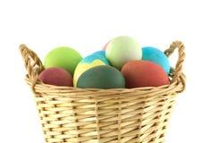 Huevos de Pascua del color en la cesta marrón aislada Foto de archivo libre de regalías