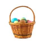 Huevos de Pascua del color en la cesta marrón aislada Imagen de archivo libre de regalías