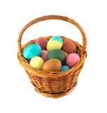 Huevos de Pascua del color en la cesta marrón aislada Imágenes de archivo libres de regalías