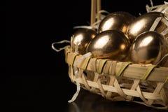 Huevos de Pascua del oro en un fondo negro Imágenes de archivo libres de regalías