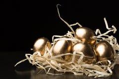 Huevos de Pascua del oro en un fondo negro Fotos de archivo