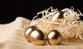 Huevos de Pascua del oro en un fondo negro Fotos de archivo libres de regalías