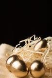 Huevos de Pascua del oro en un fondo negro Imagen de archivo libre de regalías