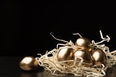 Huevos de Pascua del oro en un fondo negro Imagen de archivo