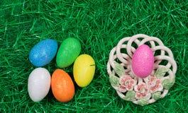 Huevos de Pascua de diversos colores que brillan en hierba verde y cuenco decorativo fotos de archivo libres de regalías
