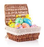 Huevos de Pascua en cesta con las flores amarillas Foto de archivo libre de regalías