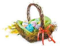 Huevos de Pascua en cesta con las flores de la primavera Fotografía de archivo