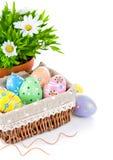 Huevos de Pascua en cesta con las flores del resorte Foto de archivo
