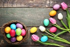 Huevos de Pascua en cesta con los tulipanes Imagen de archivo
