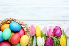 Huevos de Pascua en cesta con los tulipanes Fotos de archivo