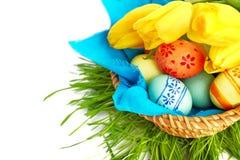 Huevos de Pascua en cesta con los tulipanes Foto de archivo libre de regalías