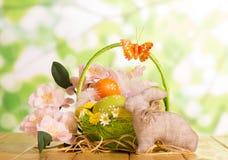 Huevos de Pascua en cesta, conejito y flores en verde abstracto Fotografía de archivo libre de regalías