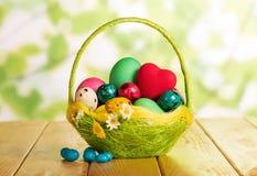 Huevos de Pascua en cesta, corazón y caramelo en verde abstracto Fotos de archivo libres de regalías