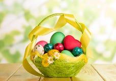 Huevos de Pascua en cesta, corazón y cinta en verde abstracto Foto de archivo