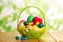 Huevos de Pascua en cesta, corazones rojos, flores y caramelo Foto de archivo libre de regalías