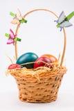 Huevos de Pascua en cesta de mimbre en blanco Fotos de archivo libres de regalías