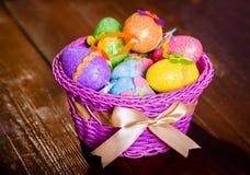 Huevos de Pascua en cesta del violett Fotos de archivo libres de regalías