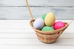 Huevos de Pascua en cesta en la madera blanca Imagenes de archivo