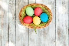 Huevos de Pascua en cesta en tablones de madera rústicos Spase para el texto Fotos de archivo libres de regalías