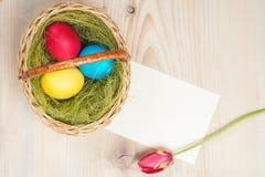 Huevos de Pascua en cesta en tablones de madera rústicos Spase para el texto Visión superior Foto de archivo libre de regalías