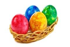 Huevos de Pascua en cesta en un fondo blanco Fotografía de archivo
