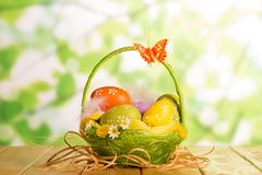 Huevos de Pascua en cesta, mariposa y cinta en verde abstracto Foto de archivo
