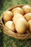 Huevos de Pascua en cesta natural marrón Imagen de archivo libre de regalías