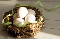 Huevos de Pascua en cesta rural con la cinta verde Huevos del pollo en un primer de la jerarquía fotografía de archivo libre de regalías