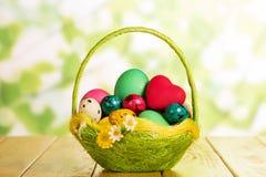 Huevos de Pascua en cesta y corazón rojo en verde abstracto Fotos de archivo libres de regalías