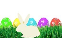 Huevos de Pascua en el conejo de la hierba verde y del papel aislado en blanco Foto de archivo