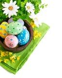Huevos de Pascua en el crisol con las flores Foto de archivo libre de regalías
