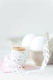 Huevos de Pascua en el fondo de madera blanco con el sobre rosado Imagenes de archivo