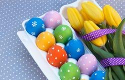Huevos de Pascua en el paquete con las flores Imagenes de archivo