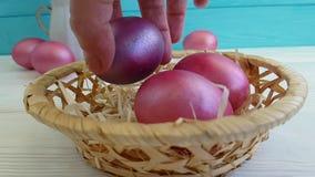 Huevos de Pascua en el tiroteo lento decorativo de la composición de mano de la cesta,