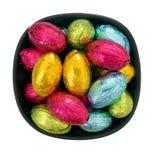 Huevos de Pascua en embalaje flexible del chocolate en el cuenco, aislado sobre blanco Imagen de archivo libre de regalías