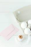 Huevos de Pascua en fondo de madera con el sobre rosado Fotografía de archivo