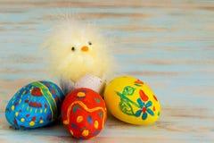 Huevos de Pascua en fondo de madera al lado de la cesta con el pollo del bebé Fotografía de archivo libre de regalías