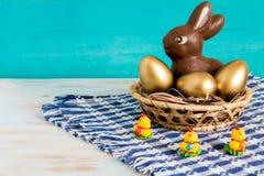 Huevos de Pascua en fondo de madera al lado de la cesta con el pollo del bebé Imagenes de archivo