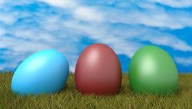 Huevos de Pascua en gras con un cielo nublado azul Imagen de archivo libre de regalías