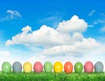 Huevos de Pascua en hierba verde sobre el cielo azul nublado Fotografía de archivo