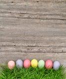 Huevos de Pascua en hierba verde sobre fondo de madera Imagen de archivo libre de regalías