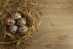 Huevos de Pascua en jerarquía en fondo de madera Imagenes de archivo