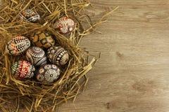 Huevos de Pascua en jerarquía en fondo de madera Imagen de archivo libre de regalías