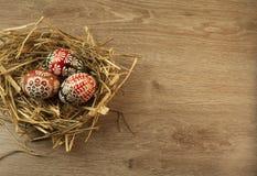 Huevos de Pascua en jerarquía en fondo de madera Fotos de archivo