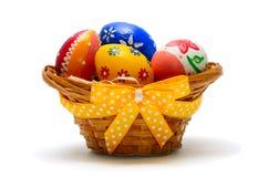 Huevos de Pascua en la cesta adornada con la cinta Imagenes de archivo